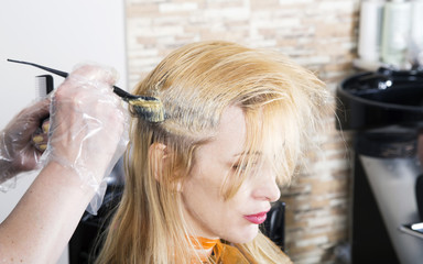 Hairdresser dyes long blond hair