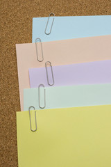 Papers with paper clip attached on the brown board