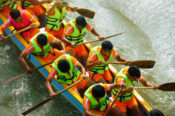 people rowing dragon boat in racing
