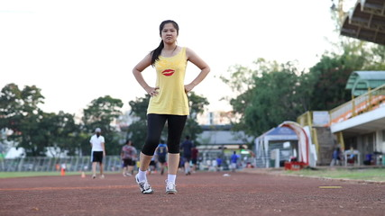 Beautiful asian woman stretching legs before running