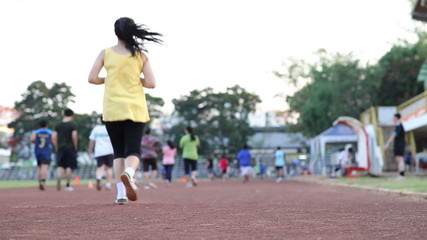 young woman jogging in the stadium park in summer