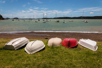 boats lying upside down on shore in Bay of Islands