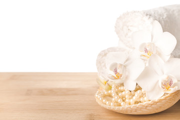 Spa still life of white orchid flower, towel and shell with bead