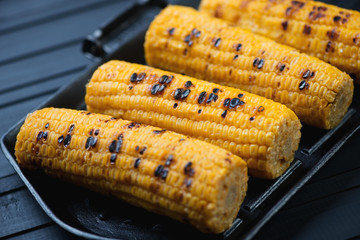 Grill with roasted sweetcorn, close-up, horizontal shot