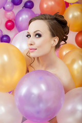 Portrait of flirty brunette posing with balloons