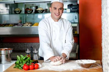 Smiling chef preparing pizza base
