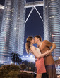 Young couple kissing on background two Petronas Twin Towers