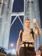 Young man photographing himself in front of two famous Petronas