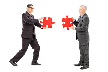 Businessmen connecting two pieces of puzzle