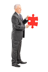 Mature businessman holding a piece of puzzle
