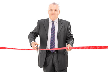 Mature businessman cutting a red tape