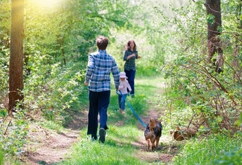 Family with dog doing morning excercises in the forest. Mom with