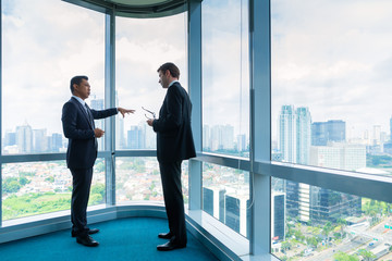 Businessmen standing in front of office window