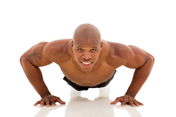 young African man doing pushups on floor