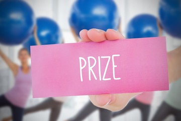 Woman holding pink card saying prize