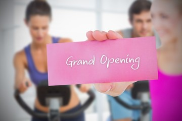 Fit blonde holding card saying grand opening