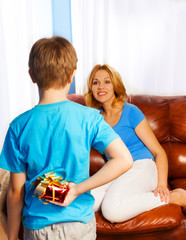 Boy holds present behind to surprise  mother