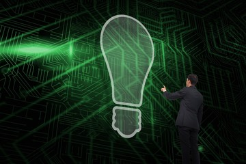 Composite image of light bulb and businessman pointing