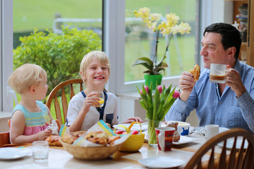Father with kids having healthy breakfast in kitchen