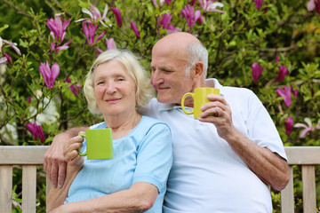 Senior couple drinking tea sitting in the garden