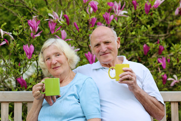 Happy loving senior couple drinking tea from big colorful mugs