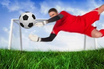 Fit goal keeper jumping up saving ball