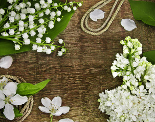 Lily of the valley, lilac and rope on a wooden table