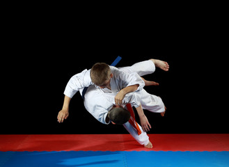 Two young athletes in the sharp drop perform judo throw
