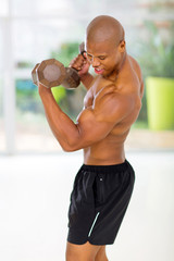 african man exercising in gym with dumbbells