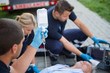 Paramedic holding drip while helping man