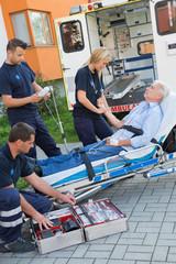 Paramedic team assisting injured man on stretcher