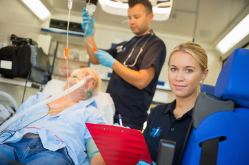 Paramedic treating unconscious man in ambulance