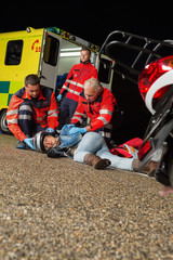 Emergency team helping injured motorbike driver