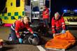 Emergency team assisting injured motorbike driver