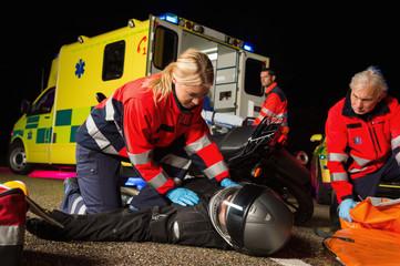 Paramedical team assisting injured motorbike driver