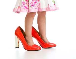 Little girl in big mommy shoes isolated on white