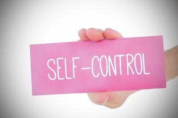 Woman holding pink card saying self control