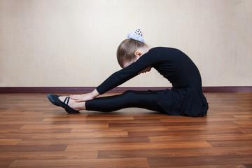 little girl gymnast sitting on the floor