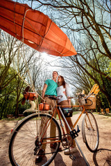 Lovely young couple standing and hugging behind the bicycle with
