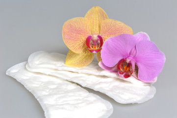Sanitary towels with orchid flowers on gray