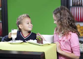 Sister and brother enjoying meal sitting at restaurant table