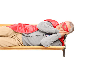 Senior man in superhero costume sleeping on bench