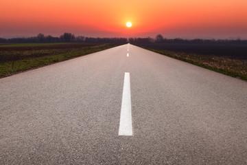 Driving on asphalt road towards the setting sun