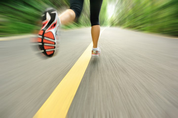 woman runner athlete legs running on road. woman fitness jogging