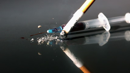 Cigarette and syringe falling onto reflective surface