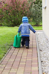 Child with watering can in the garden