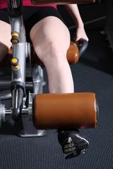 Frau im Fitnessstudio trainiert auf Beinstrecker