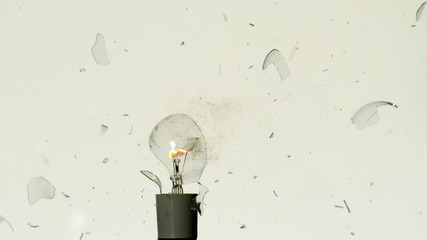 Arrow shooting through light bulb on white background