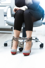businesswomen legs being locked by chain