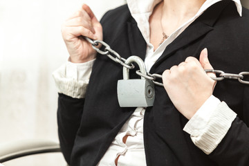 photo of businesswoman being locked by chain and padlock